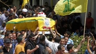 Men carry the coffin of a Hezbollah member allegedly killed while fighting in the Syrian town of Qusair, during his funeral in Beirut, Lebanon (22 May 2013)