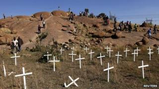 People walk near crosses placed at the site where 34 miners were killed in South Africa (14 May 2013)