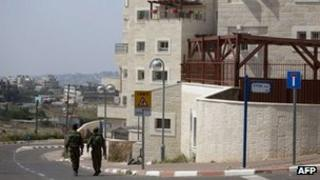 Israeli soldiers walk in the West Bank settlement of Beit El