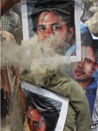In this Thursday, May 16, 2013 photo, Indian people burn an effigy with posters of Indian cricketer Shanthakumaran Sreesanth at a protest against spot fixing during the Indian Premier League (IPL) in Bangalore, India. A