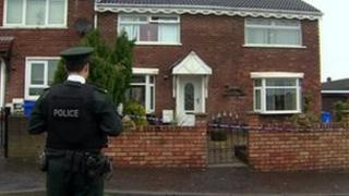 The woman was found dead at a house in west Belfast