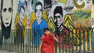 A young boy walks past graffiti images of those killed in the revolution in Tahrir Square