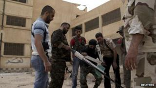 Free Syrian Army fighters prepare to launch a rocket in Deir al-Zor