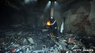 A Tunisian fire fighter inside a burnt out building in the grounds of the American school in Tunis on September 2012