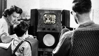 Composite image showing a family watching TV in the 1950s [image: Getty], with footage from the coronation superimposed on top
