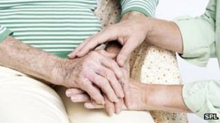 Person holds elderly woman's hand