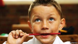 A boy thinking with a pencil in his mouth