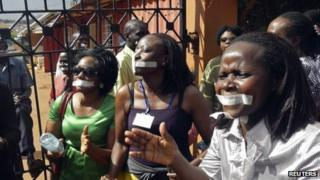 Employees of the Daily Monitor newspaper with their mouths taped shut, sing slogans during a protest against the closure of their premises by the Uganda government, outside their offices in the capital, Kampala, on 20 May 2013