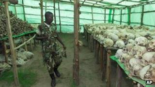 A Rwandan soldier looks at the hundreds of human skulls and remains of genocide victims at the genocide memorial in Bisesero, Rwanda