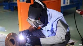 An factory worker welds at an air conditioner manufacturing facility near Ahmedabad