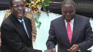 Zimbabwean President Robert Mugabe (L) shakes hands with Prime Minister Morgan Tsvangirai after he signed the new constitution into law at State house in Harare on Wednesday 22 May 2013