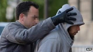 Police officer escorts the suspect in the case of a French soldier stabbed into police headquarters
