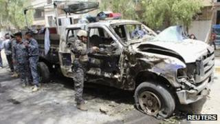 Iraqi security personnel inspect the site of a bomb attack in a district of Baghdad