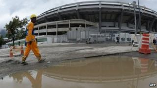 A workman walks past a large puddle outside Rio de Janeiro's Maracana football stadium