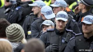 A police officer with blood on his face looks on as Unite Against Fascism (UAF) supporters protest