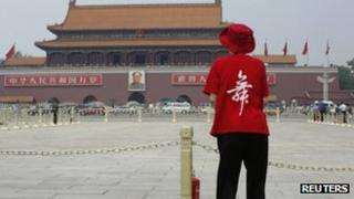 "A woman wearing a T-Shirt saying ""Dance"" stands in Tiananmen Square (31 May 2013)"