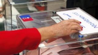 hand putting vote into ballot box