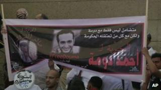 Supporters wave a banner for activist Ahmed Douma