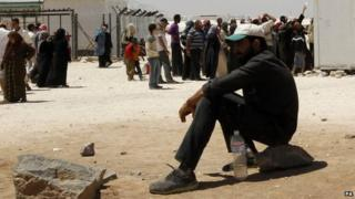 Syrian refugees wait to receive aid and rations