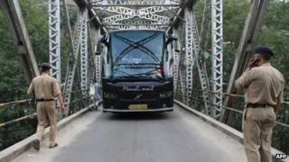 Police stop a tourist bus at a checkpoint put in place following the rape of a US tourist in the Indian town of Manali on 5 June 5, 2013