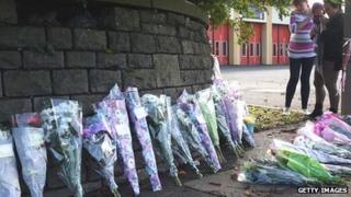 People stop to look at the growing number of floral tributes being left outside Ely Fire Station