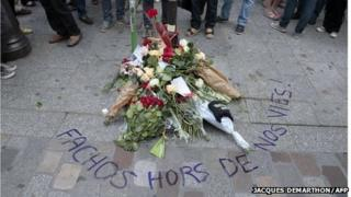 """Flowers and text reading """"Fascists get out of our lives"""" near the spot where Clement Meric was killed"""