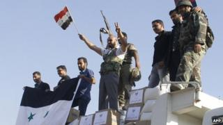 Forces loyal to the Syrian army wave national flags as they celebrate in the main square of Qusair in Syria's central Homs province