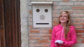 Girl standing by letterbox face