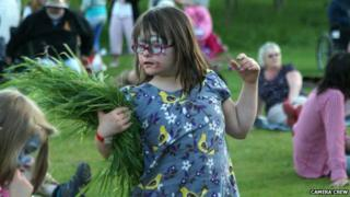 A girl dances while wearing face paint and holding a sheaf of grass