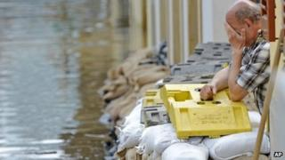 A man reacts outside a flooded house in Dresden