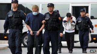 Suspects Hu Tsung-hsien (2nd left) and Chu Ya-dong (4th from left) being escorted to Taiwan's Criminal Investigation Bureau in Taipei on 16 April 2013