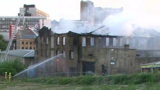 Fire fighters hosing down smouldering mill