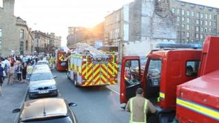 Fire engines and crowds outside the mill