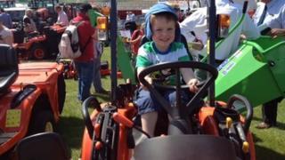 Boy on farm machinery
