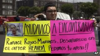 A man holds a placard asking for help with the search of a group of missing youngsters in Mexico City on 40 May 2013