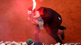 Security guard restrains flare-wielding protester, French Open, Paris (9 June)
