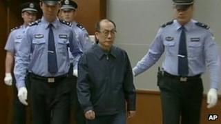 Former Chinese Railways Minister Liu Zhijun, second from right, is escorted into a courtroom in Beijing on 9 June 2013