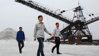 Workers walking on a salt field in China