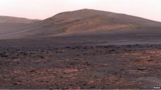 The surface of Mars with a mountain in the distance called Solander Point.