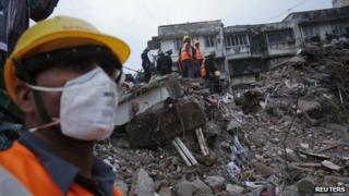 Rescuers search through the rubble at the site of a collapsed residential building in Mumbai on 11 June 2013