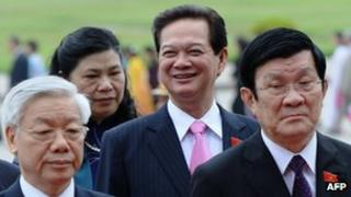 Prime Minister Nguyen Tan Dung (second on the right) smiling as he walks behind Vietnamese communist party Secretary General Nguyen Phu Trong (left) and President Truong Tan Sang (right) in October 2012