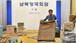 """A South Korean worker removes office fixtures at the venue for the inter-Korean talks after their cancellation at a hotel in Seoul on 12 June 2013. The Korean letters read """"South and North Korean Governments Meeting"""""""