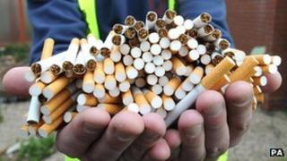 A pair of hands holding a large amount of cigarettes