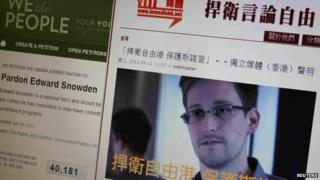 A statement by Hong Kong online media In Media Hong Kong supporting Edward Snowden is displayed alongside a petition to Pardon Edward Snowden on a White House website, on a computer screen in Hong Kong on 12 June 2013
