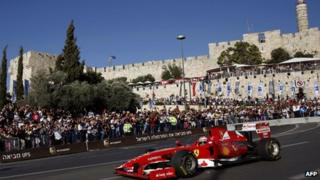 Three-time F1 Grand Prix winner Giancarlo Fisichella drives his Ferrari Formula 1 car below the ancient walls of Jerusalem's Old City on June 13, 2013 during the first Jerusalem F1 Peace Roadshow.