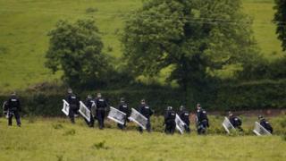 Riot police patrol the fields close to Lough Erne Golf Resort, Enniskillen