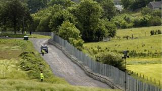 Police patrol the massive metal fence that surrounds the Lough Erne Golf Resort, Enniskillen