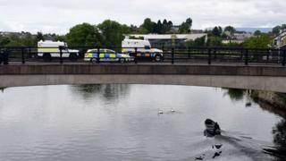 Police officers stand by their armoured vehicles on a bridge in Enniskillen