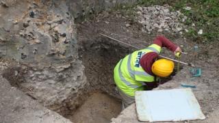 An archaeologist takes a measurement at the 12th Century Saffron Walden Castle