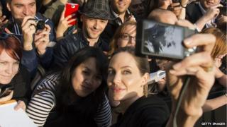 Angelina Jolie, surrounded by fans, taking a 'selfie'